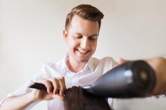 Ευτυχής στιλίστας με τον ανεμιστήρα που κάνει χτύπημα-ξηρό στο σαλόνι στοκ εικόνες