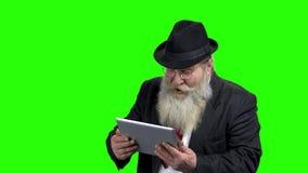 Ευτυχής συγκλονισμένος ηληκιωμένος που εξετάζει το PC ταμπλετών απόθεμα βίντεο