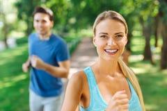 Ευτυχής συμπαθητική γυναίκα που απολαμβάνει το τρέξιμο στο πάρκο στοκ φωτογραφία