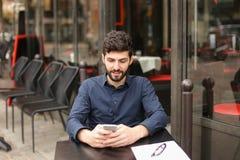 Ευτυχής συνεδρίαση ατόμων στον πίνακα καφέδων και να κουβεντιάσει από το smartphone με Στοκ Εικόνες