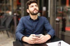 Ευτυχής συνεδρίαση ατόμων στον πίνακα καφέδων και να κουβεντιάσει από το smartphone με Στοκ Φωτογραφία