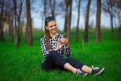 Ευτυχής συνεδρίαση δακτυλογράφησης κοριτσιών sms στο πάρκο στη χλόη Γυναίκα που κουβεντιάζει στο τηλέφωνο Στοκ φωτογραφία με δικαίωμα ελεύθερης χρήσης