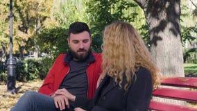 Ευτυχής συνεδρίαση ζευγών στον πάγκο στο πάρκο απόθεμα βίντεο