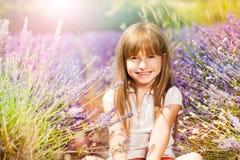 Ευτυχής συνεδρίαση κοριτσιών στο έδαφος lavender στον τομέα Στοκ φωτογραφία με δικαίωμα ελεύθερης χρήσης