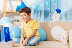Ευτυχής συνεδρίαση μικρών παιδιών στον καναπέ και χαμόγελο ευτυχώς Στοκ Εικόνα