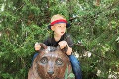 Ευτυχής συνεδρίαση αγοριών στο άγαλμα αρκούδων στο ζωολογικό κήπο Στοκ Εικόνα