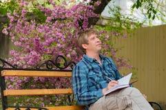 Ευτυχής συνεδρίαση ατόμων στον πάγκο ένα πάρκο Στοκ Φωτογραφία