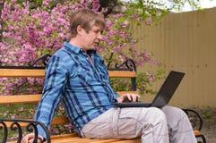 Ευτυχής συνεδρίαση ατόμων στον πάγκο και χρησιμοποίηση του lap-top σε ένα πάρκο Στοκ Εικόνες