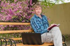 Ευτυχής συνεδρίαση ατόμων στον πάγκο και χρησιμοποίηση του lap-top σε ένα πάρκο Στοκ Φωτογραφία