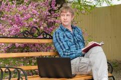 Ευτυχής συνεδρίαση ατόμων στον πάγκο και χρησιμοποίηση του lap-top σε ένα πάρκο Στοκ Εικόνα