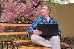 Ευτυχής συνεδρίαση ατόμων στον πάγκο και χρησιμοποίηση του lap-top σε ένα πάρκο Στοκ εικόνες με δικαίωμα ελεύθερης χρήσης