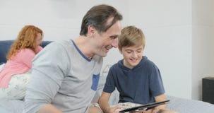 Ευτυχής συνεδρίαση γέλιου υπολογιστών ταμπλετών χρήσης πατέρων και γιων στο κρεβάτι στο χρόνο εξόδων κρεβατοκάμαρων από κοινού απόθεμα βίντεο