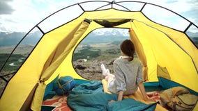 Ευτυχής συνεδρίαση γυναικών σε μια σκηνή, άποψη των βουνών απόθεμα βίντεο