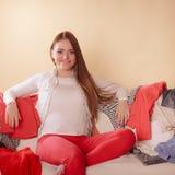Ευτυχής συνεδρίαση γυναικών στον καναπέ στο ακατάστατο δωμάτιο στο σπίτι Στοκ Φωτογραφία