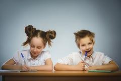 Ευτυχής συνεδρίαση κοριτσιών και αγοριών στο γραφείο στο γκρίζο υπόβαθρο μαύρο σχολείο έννοιας βιβλίων ανασκόπησης copyspace Στοκ Φωτογραφία