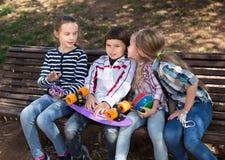 Ευτυχής συνεδρίαση κοριτσιών και αγοριών στο πάρκο σε έναν πάγκο την άνοιξη Στοκ Εικόνες