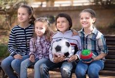 Ευτυχής συνεδρίαση κοριτσιών και αγοριών στο πάρκο σε έναν πάγκο Στοκ Εικόνα