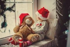 Ευτυχής συνεδρίαση κοριτσιών παιδιών πίσω στα Χριστούγεννα χειμερινών παραθύρων Στοκ εικόνα με δικαίωμα ελεύθερης χρήσης