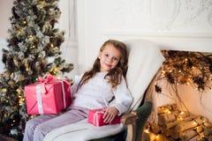 Ευτυχής συνεδρίαση κοριτσιών παιδιών στην πολυθρόνα που καλύπτεται με ένα κάλυμμα ενάντια στη διακοσμημένη εστία Χριστουγέννων Στοκ εικόνες με δικαίωμα ελεύθερης χρήσης