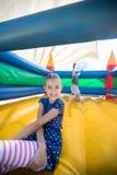 Ευτυχής συνεδρίαση κοριτσιών στο κάστρο bouncy ενώ αδελφός που κάνει handstand στο υπόβαθρο Στοκ Φωτογραφία