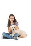 Ευτυχής συνεδρίαση μικρών κοριτσιών με το σκυλί στα πόδια της Στοκ Φωτογραφία
