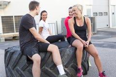 Ευτυχής συνεδρίαση ομάδων workout σε μια ρόδα και λήψη ενός σπασίματος υπαίθριου στοκ εικόνες