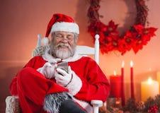 Ευτυχής συνεδρίαση santa στην καρέκλα και χρησιμοποίηση του κινητού τηλεφώνου Στοκ Φωτογραφίες