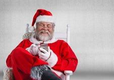 Ευτυχής συνεδρίαση santa στην καρέκλα και χρησιμοποίηση του κινητού τηλεφώνου Στοκ Φωτογραφία
