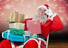 Ευτυχής συνεδρίαση santa στην καρέκλα με τα δώρα Χριστουγέννων Στοκ Φωτογραφίες