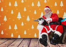 Ευτυχής συνεδρίαση santa στον καναπέ και το βιβλίο ανάγνωσης Στοκ φωτογραφία με δικαίωμα ελεύθερης χρήσης