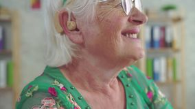 Ευτυχής συνταξιούχος γυναίκα που φορά μια ενίσχυση ακρόασης φιλμ μικρού μήκους