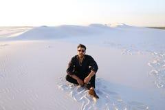 Ευτυχής συντροφικός Άραβας, κάθεται μέσω της ερήμου, χαμογελά και απολαμβάνει lif Στοκ εικόνες με δικαίωμα ελεύθερης χρήσης