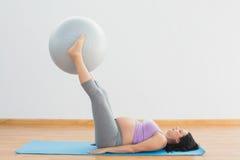 Ευτυχής σφαίρα άσκησης εγκύων γυναικών ανυψωτική με τα πόδια Στοκ Εικόνες