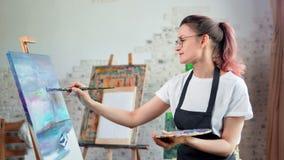 Ευτυχής ταλαντούχος νέος ζωγράφος γυναικών που απολαμβάνει την εικόνα σχεδίων στο μέσο πυροβολισμό στούντιο τέχνης φιλμ μικρού μήκους