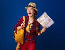 Ευτυχής ταξιδιωτική γυναίκα που απομονώνεται στο μπλε υπόβαθρο με το χάρτη στοκ εικόνα