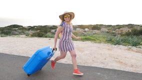 Ευτυχής ταξιδιωτική γυναίκα που τρέχει με τη βαλίτσα φιλμ μικρού μήκους