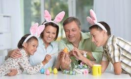 Ευτυχής τετραμελής οικογένεια που φορά τα αυτιά λαγουδάκι και που χρωματίζει Πάσχα τα αυγά Στοκ Εικόνες