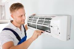 Ευτυχής τεχνικός που επισκευάζει το κλιματιστικό μηχάνημα στοκ εικόνα με δικαίωμα ελεύθερης χρήσης