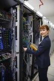 Ευτυχής τεχνικός που χρησιμοποιεί την ψηφιακή συσκευή ανάλυσης καλωδίων στον κεντρικό υπολογιστή Στοκ Εικόνα