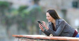 Ευτυχής τηλεφωνικό περιεκτικότητα σε ξεφυλλίσματος γυναικών σε ένα μπαλκόνι απόθεμα βίντεο