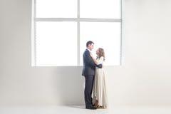Ευτυχής τοποθέτηση γαμήλιων ζευγών στο φωτεινό δωμάτιο που αγκαλιάζει το ένα το άλλο στοκ εικόνες
