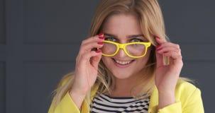 Ευτυχής τοποθέτηση γυναικών με κίτρινα eyeglasses στο στούντιο φιλμ μικρού μήκους