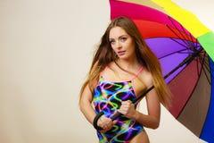 Ευτυχής τοποθέτηση γυναικών στο μαγιό και τη ζωηρόχρωμη ομπρέλα Στοκ Φωτογραφίες