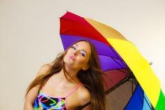 Ευτυχής τοποθέτηση γυναικών στο μαγιό και τη ζωηρόχρωμη ομπρέλα στοκ εικόνα