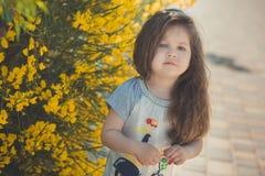 Ευτυχής τοποθέτηση κοριτσιών παιδιών κατά τη διάρκεια των θερινών διακοπών κοντά στα κίτρινα λουλούδια πάρκων Στοκ φωτογραφία με δικαίωμα ελεύθερης χρήσης