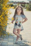 Ευτυχής τοποθέτηση κοριτσιών παιδιών κατά τη διάρκεια των θερινών διακοπών κοντά στα κίτρινα λουλούδια πάρκων Στοκ εικόνα με δικαίωμα ελεύθερης χρήσης