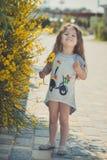 Ευτυχής τοποθέτηση κοριτσιών παιδιών κατά τη διάρκεια των θερινών διακοπών κοντά στα κίτρινα λουλούδια πάρκων Στοκ εικόνες με δικαίωμα ελεύθερης χρήσης