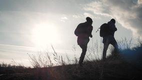 Ευτυχής τουρίστας ανδρών και γυναικών ζευγών στην κορυφή του βουνού στο ηλιοβασίλεμα υπαίθρια κατά τη διάρκεια ενός πεζοπορώ Σκια απόθεμα βίντεο