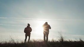 Ευτυχής τουρίστας ανδρών και γυναικών ζευγών στην κορυφή του βουνού στο ηλιοβασίλεμα υπαίθρια κατά τη διάρκεια ενός πεζοπορώ Σκια φιλμ μικρού μήκους