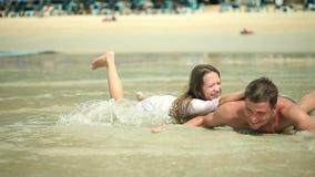Ευτυχής το ενήλικο ζεύγος που έχει τη διασκέδαση και που παίζει στη θάλασσα απόθεμα βίντεο